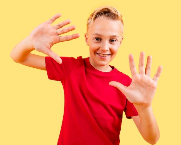 Figlarny chłopiec pokazano obie ręce w wolnym nastroju