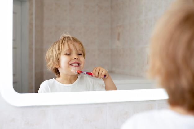 Figlarny chłopiec szczotkuje zęby