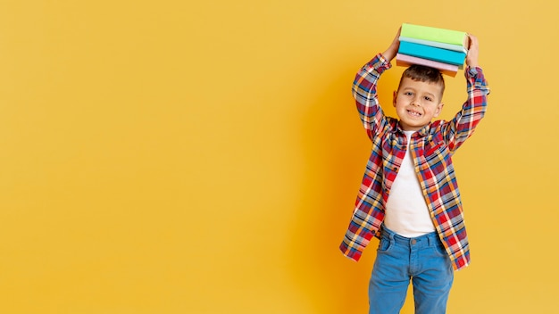 Figlarny chłopiec ze stosem książek na głowie