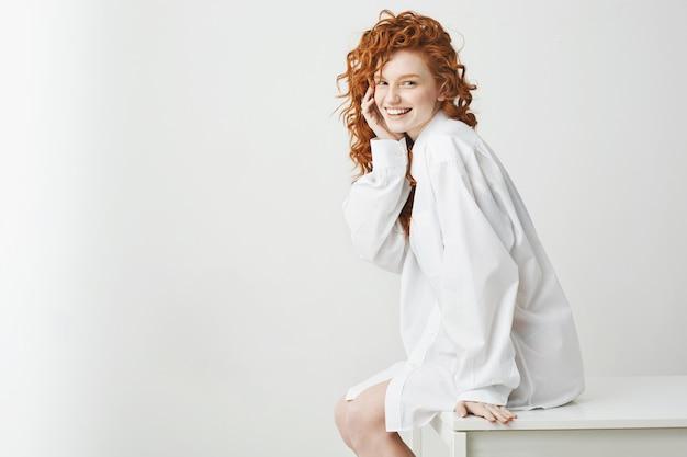 Figlarny dość delikatna kobieta z kręconymi rudymi włosami, śmiejąc się, siedząc na stole na białej ścianie