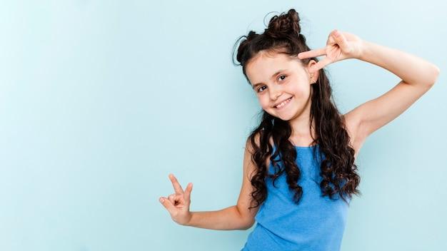 Figlarny dziewczyna pokazując znak pokoju