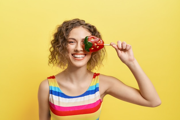 Figlarny dziewczyna ukrywa oko z lollipop truskawki cukierki.