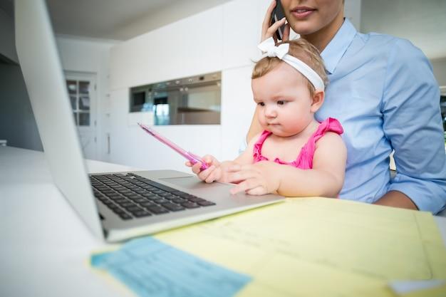 Figlarny dziewczynka siedzi z matką przez laptopa