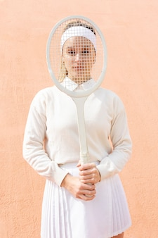 Figlarny kobieta obejmujących twarz z rakieta tenisowa