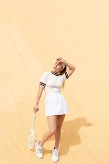 Figlarny kobieta tenisista z rakietą