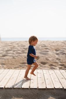 Figlarny mały chłopiec biegną na plaży