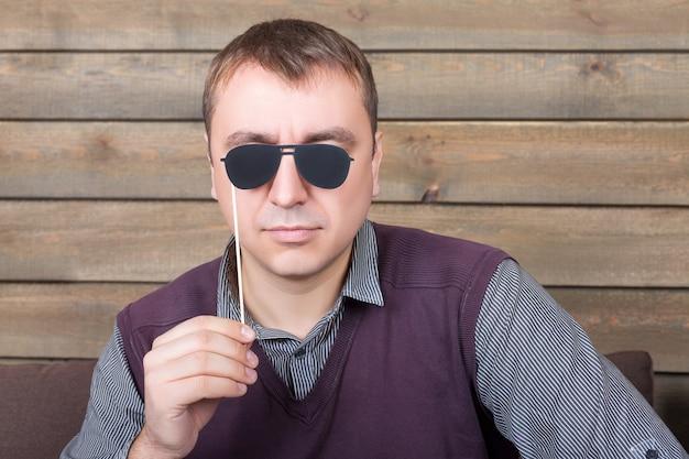 Figlarny mężczyzna z śmiesznymi okularami przeciwsłonecznymi na patyku