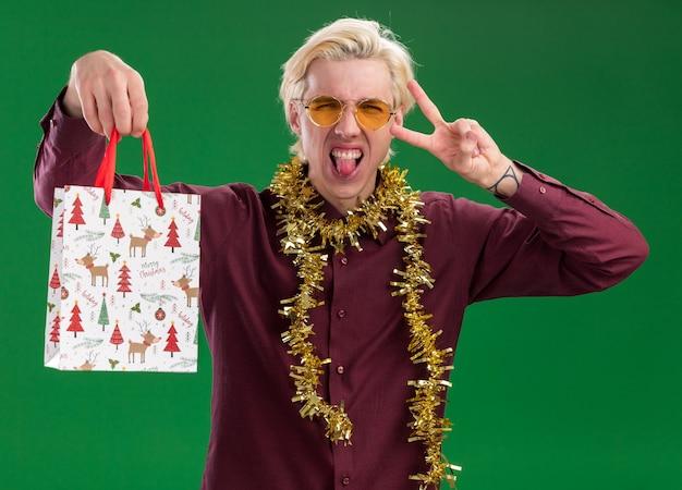 Figlarny młody blondyn w okularach z świecącą girlandą na szyi trzyma torbę z prezentami świątecznymi patrząc na kamerę pokazującą język i robi znak pokoju na białym tle na zielonym tle