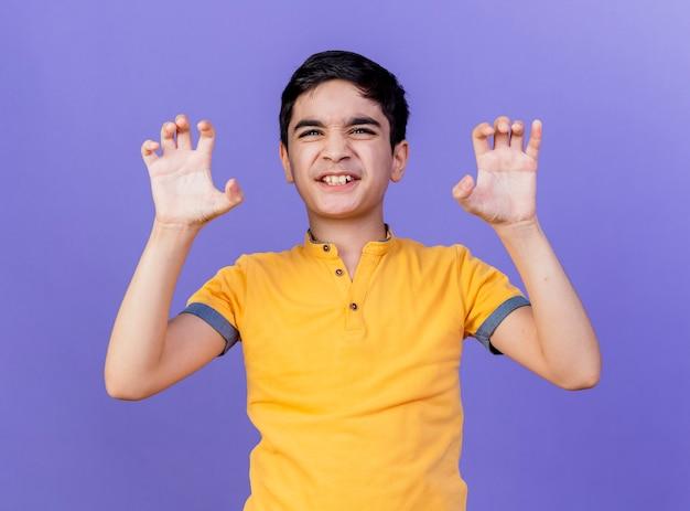 Figlarny młody chłopiec kaukaski robi ryk tygrysa i gest łapy na białym tle na fioletowej ścianie