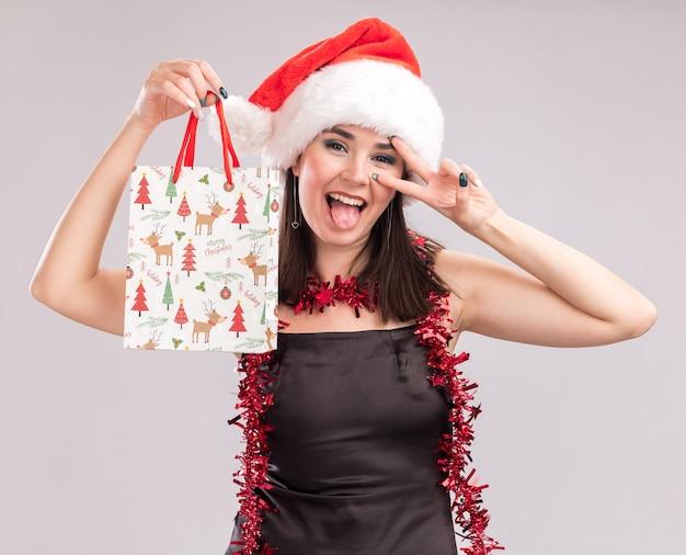 Figlarny młody ładny kaukaski dziewczyna nosi santa hat i blichtr girlandę wokół szyi trzymając świąteczną torbę prezentową, patrząc na kamerę pokazującą symbol języka i znaku v w pobliżu oka na białym tle