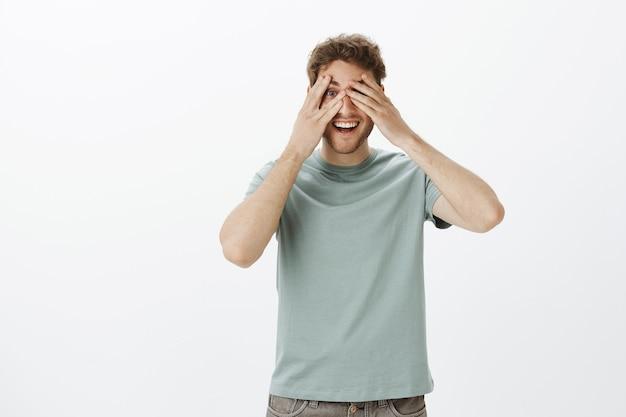 Figlarny model szczęśliwego mężczyzny w t-shircie, zakrywający oczy dłońmi i zaglądający przez palce, uśmiechnięty szeroko