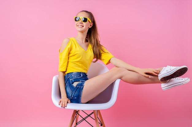 Figlarny nastolatka siedzi na krześle z podniesionymi nogami