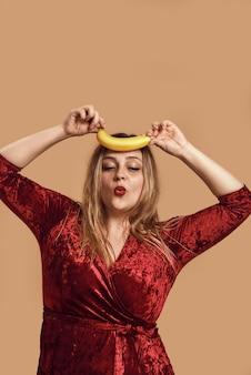 Figlarny nastrój studio strzał plus size kobiety w czerwonej welurowej sukience trzymającej banana powyżej