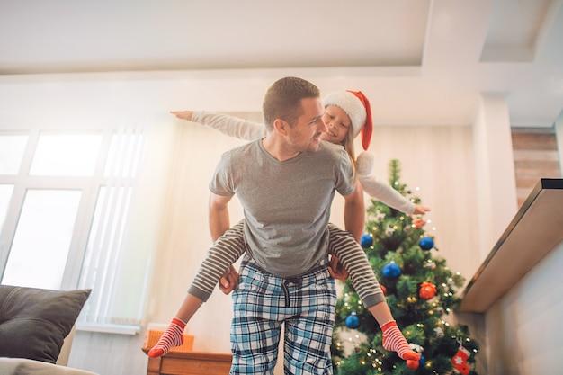 Figlarny obrazek przedstawiający szczęśliwego ojca i córkę spędzających razem czas. ujeżdża ją na plecach.