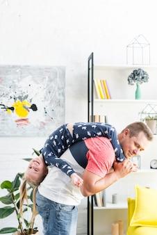 Figlarny ojciec niosąc jej szczęśliwą córkę w salonie