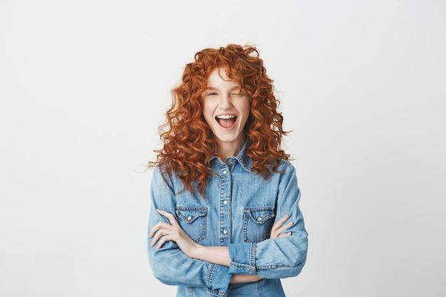 Figlarny piękna ruda dziewczyna uśmiecha się mrugając. skrzyżowane ręce.