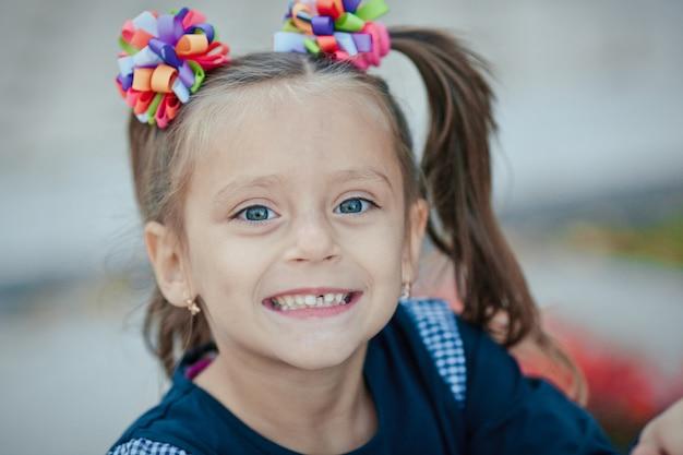 Figlarny portret dziewczynki w parku, uśmiechając się i bawiąc się na łonie natury