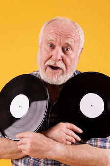 Figlarny senior trzyma płyty z muzyką