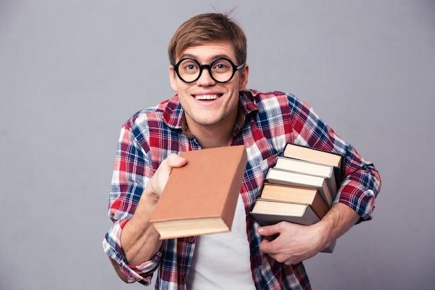 Figlarny szczęśliwy młody człowiek w kraciastej koszuli i zabawnych okrągłych okularach, dający ci książkę na szarej ścianie