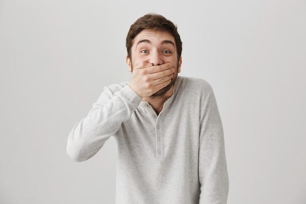 Figlarny szczęśliwy przystojny facet śmieje się, zamyka usta, żeby nie chichotać