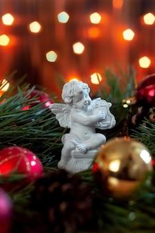 Figurka anioła grającego na harfie na gałęzi choinki na tle bokeh