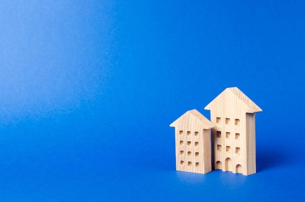 Figurka budynków mieszkalnych stoi na niebieskim tle koncepcja kupna i sprzedaży nieruchomości na wynajem
