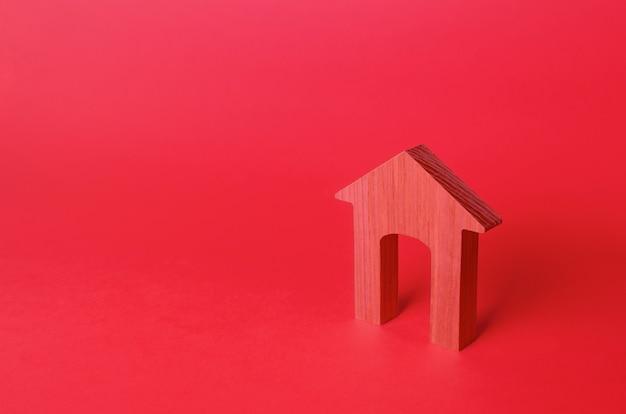 Figurka domu z czerwonego łuku niedrogie mieszkanie wynajem nieruchomości naprawa i renowacja modernizacja minimalizm czerwone tło logowania