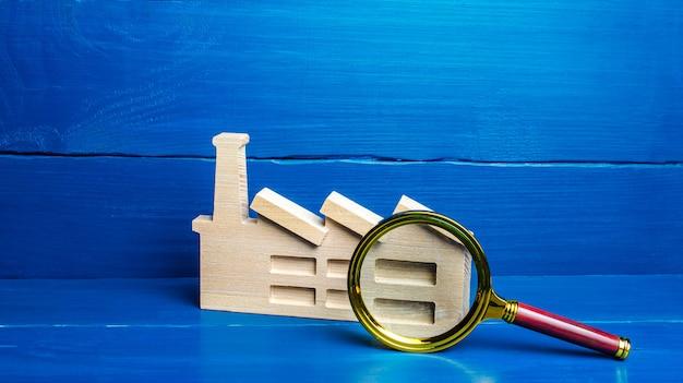 Figurka fabryki przemysłowej i szkło powiększające koncepcja monitorowania dużego biznesu