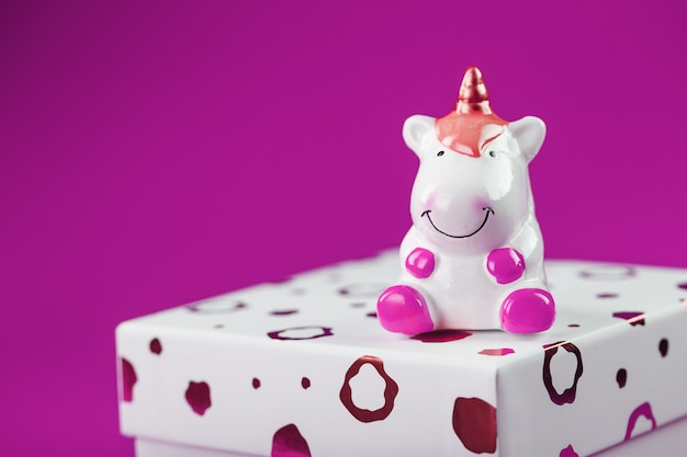 Figurka jednorożca na pudełku z prezentem na różowym tle