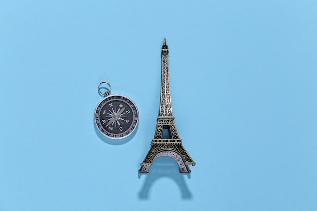 Figurka kompasu i wieży eiffla na niebieskim jasnym kolorze