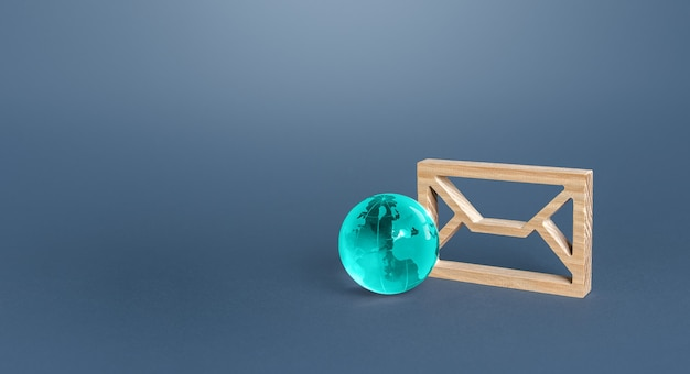 Figurka koperty pocztowej i niebieska szklana kula komunikacja przez ogólnoświatową sieć