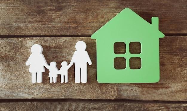 Figurka rodziny z domkiem na drewnianej powierzchni