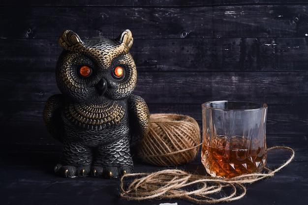 Figurka sowy, kłębek nici i kieliszek whisky. skład drogiego wypoczynku