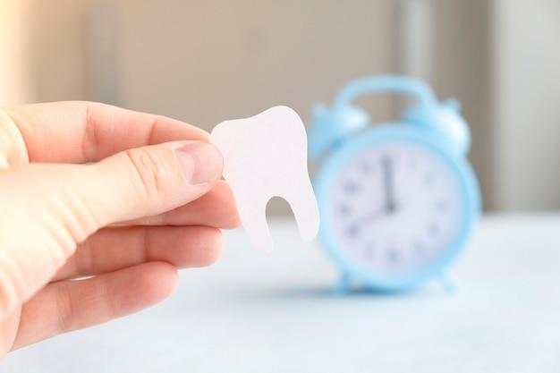 Figurka zęba w ręku na niebieskim tle. środki do pielęgnacji jamy ustnej.
