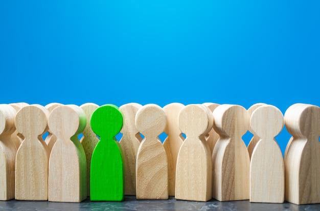 Figurka zielonego mężczyzny w tłumie ludzi rekrutacja nowych pracowników headhunterów szukaj utalentowanych pracowników