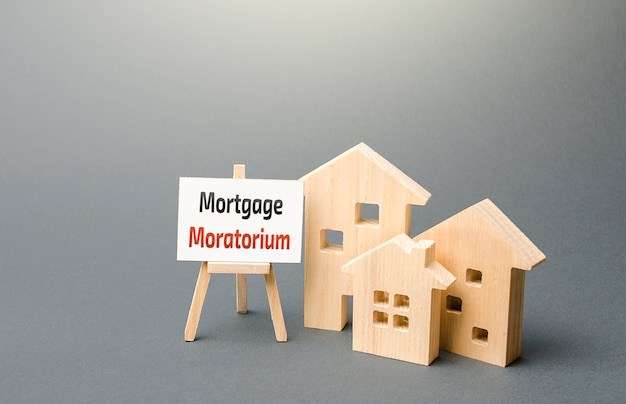 Figurki domów i tabliczka sztalugowa z mortgage moratorium moratorium na spłatę kredytów