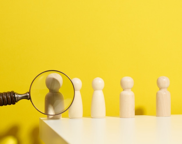 Figurki mężczyzn na białym stole i lupie. koncepcja poszukiwania pracowników w firmie, rekrutacja personelu, identyfikacja utalentowanych i silnych osobowości