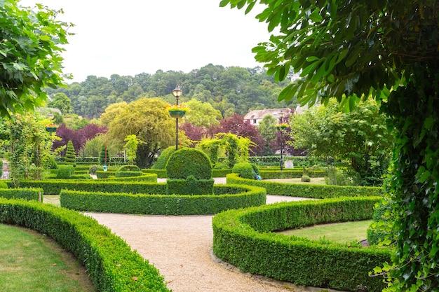 Figurki z krzaków w różnych kształtach, letni park w europie. profesjonalne ogrodnictwo, europejski zielony krajobraz, dekoracja roślin ogrodowych