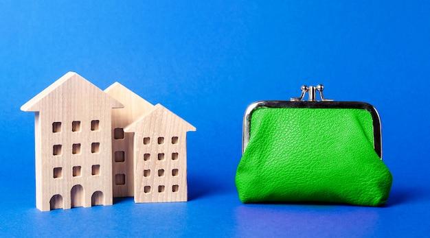 Figury budynków mieszkalnych w pobliżu dużego zielonego portfela. koszty utrzymania