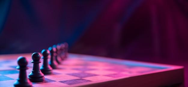 Figury szachowe na szachownicy na ciemnym tle nakręcone w neonowych różowo-niebieskich kolorach. postać w szachy. zamknij się.