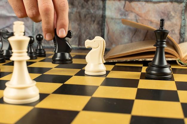 Figury szachowe ustawiają się na szachownicy. gracz gra w szachy