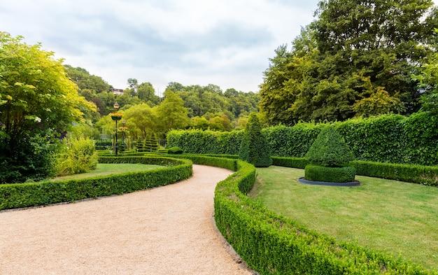 Figury w kształcie wiru i stożka z krzaków, letni park w europie. profesjonalne ogrodnictwo, europejski zielony krajobraz, dekoracja roślin ogrodowych