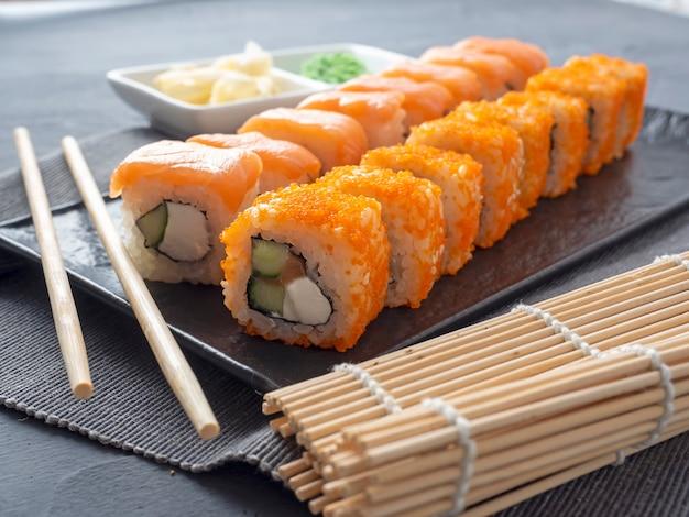 Filadelfia i kalifornia toczą się na ciemnym talerzu z teksturą. obok znajduje się wasabi, imbir i bambusowe pałeczki. widok z boku, z bliska. kuchnia japońska
