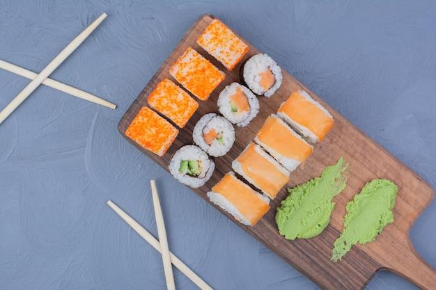 Filadelfia, łosoś i sake maki roll z wasabi na drewnianym talerzu.