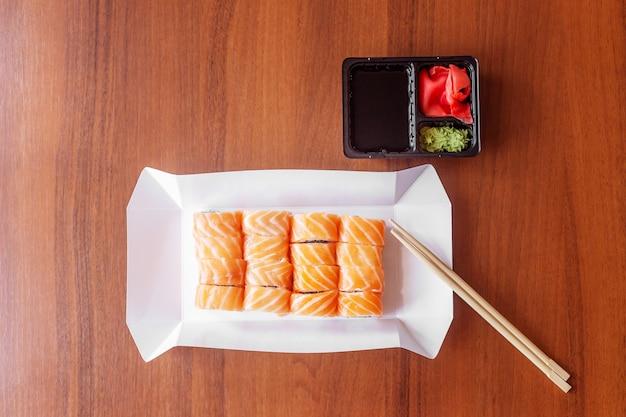 Filadelfia toczy klasykę na drewnianym stole. łosoś, ser philadelphia, ogórek, awokado, drewniane paluszki. dostawa japońskiego sushi. widok z góry, leżał płasko