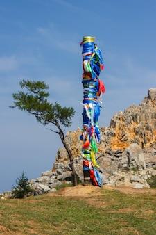 Filar szamański z wielokolorowymi wstążkami na tle przylądka burkhan, wyspa olkhon. 13 filarów na przylądku burkhan na wyspie olkhon.