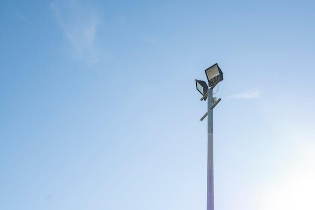 Filar z dwoma projektorami na tle błękitnego nieba