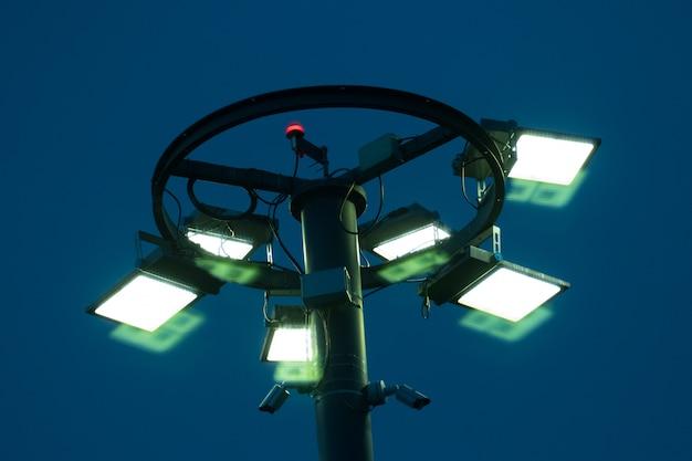 Filar z płonącymi reflektorami przy błękitną nocą.