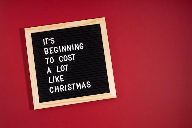 Filcowa tablica na listy z zabawnym cytatem zaczyna kosztować dużo jak boże narodzenie. spemding pieniądze na koncepcję drogich prezentów bożonarodzeniowych
