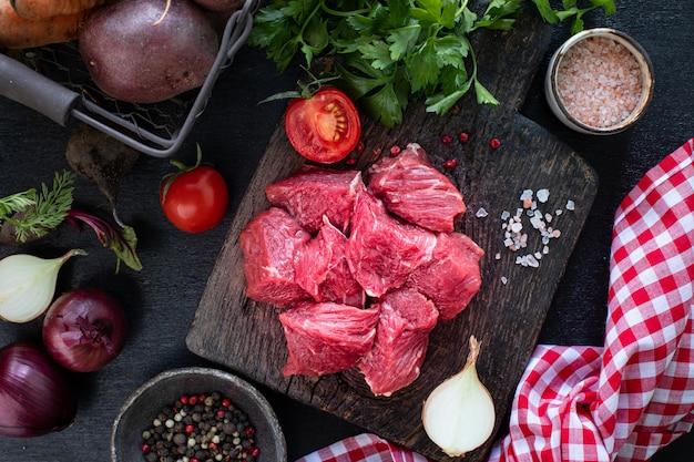 Filet cielęcy na drewnianej desce do krojenia z pomidorami koktajlowymi, ostrą papryką i ziołami.